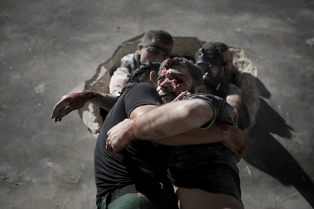 . A rebel fighter is carried down a ladder from his position in a third story apartment after being critically wounded by a Syrian government tank shell during an intense battle between rebels and Syrian army forces at the al-arqub neighborhood of Aleppo, on September 26, 2012. (ZAC BAILLIE/AFP/GettyImages)