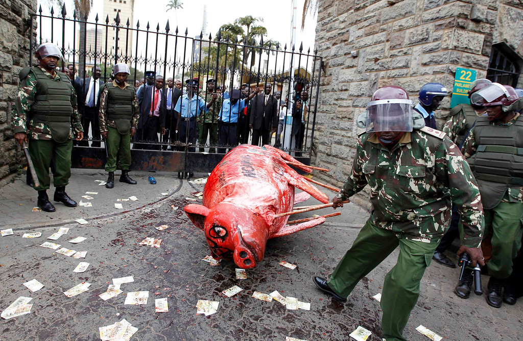 . A riot police officer removes a dummy of a pig covered with animal blood, left by protestors during a demonstration against lawmakers\' demands for a pay rise, at the entrance of the parliament buildings in Nairobi, June 11, 2013. Refusing to accept a cut imposed by the Salaries and Remuneration Commission in May, members of parliament voted to increase their salaries to 130 times the minimum wage, which according to them, are needed to deter bribery and provide charitable support for constituents. Protesters have deemed the proposed salary raise a violation of the constitution, according to news reports. REUTERS/Thomas Mukoya