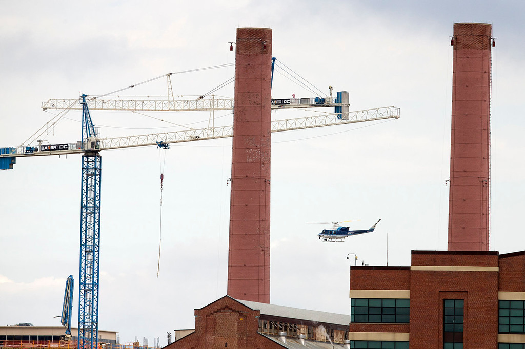 . A U.S. Park Police helicopter continues a search pattern above the scene of a shooting at the Washington Navy Yard on Monday, Sept. 16, 2013 in Washington. (AP Photo/ Evan Vucci)