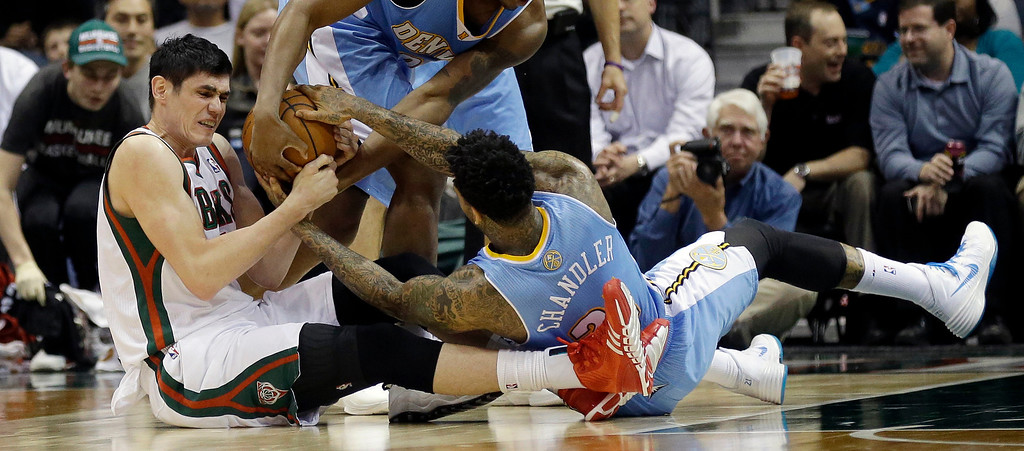 . Denver Nuggets\' Wilson Chandler (21) and Milwaukee Bucks\' Ersan Ilyasova, left, reach for a loose ball during the first half of an NBA basketball game Thursday, Feb. 20, 2014, in Milwaukee. (AP Photo/Jeffrey Phelps)