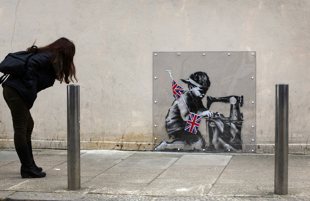 . A woman looks at an artwork attributed to Banksy under a plastic cover on May 17, 2012 in London, England. The stencilled image depicts a poor child making Union Jack flags on a sewing machine and is located on the wall of a Poundland discount shop in the Wood Green area of north London.  (Photo by Peter Macdiarmid/Getty Images)