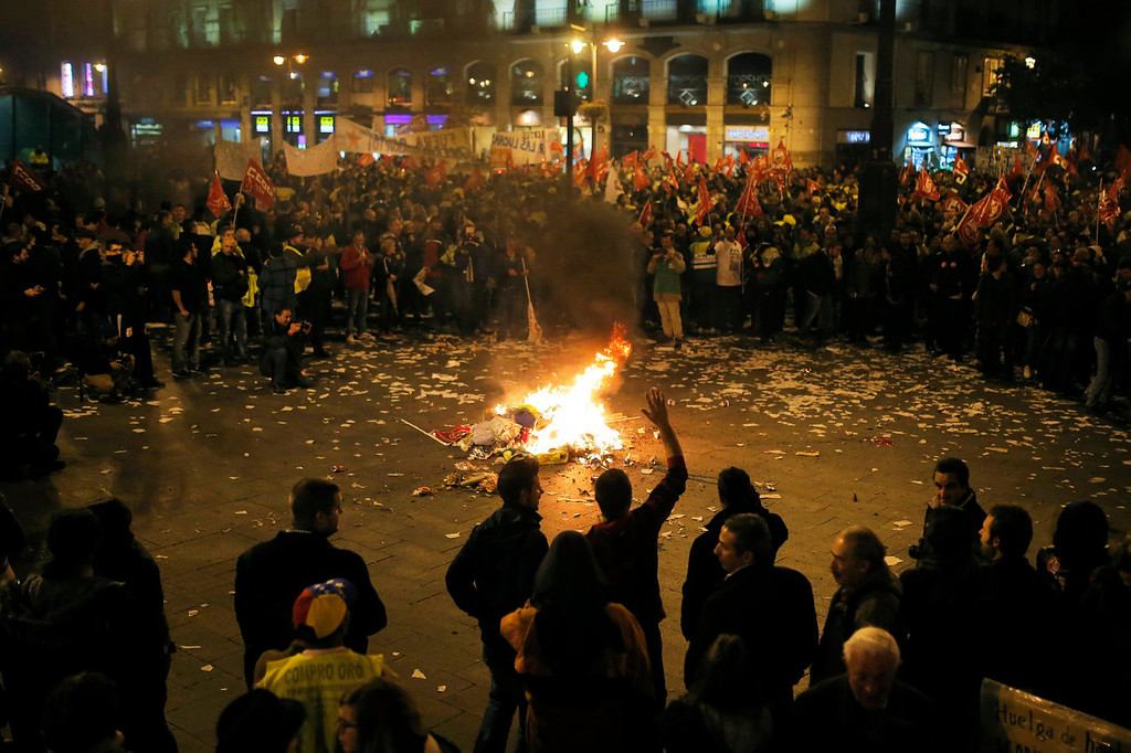 . Protestors burn trash and municipal worker uniforms during a demonstration against layoffs of street cleaners and garbage collectors in Madrid, Spain, Monday, Nov. 4, 2013. Trash collectors in Madrid have started bonfires and set off firecrackers during a noisy protest in one of the Spanish capitalís main squares as they prepare to start an open-ended strike. (AP Photo/Andres Kudacki)