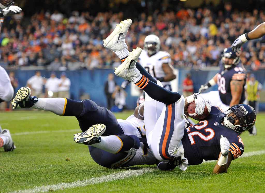 . Chicago Bears running back Matt Forte (22) rolls into the end zone for a touchdown against San Diego Chargers nose tackle Kwame Geathers (92) during the first half of the preseason NFL football game, Thursday, Aug. 15, 2013, in Chicago. (AP Photo/Jim Prisching)