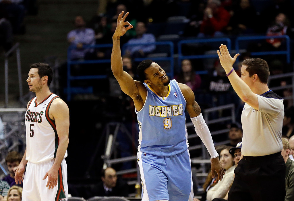 . Denver Nuggets\' Andre Iguodala (9) reacts to his 3-pointer in front of Milwaukee Bucks\' J.J. Redick (5) during the second half of an NBA basketball game, Monday, April 15, 2013, in Milwaukee. Denver won 112-111. (AP Photo/Jeffrey Phelps)