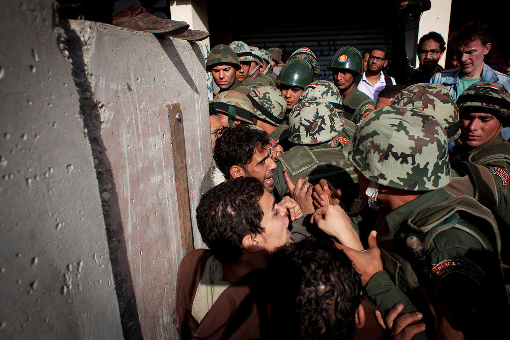 . Egyptian protesters scuffle with army soldiers near the presidential palace in Cairo, Egypt, Sunday, Dec. 9, 2012. Egypt\'s liberal opposition has called for more protests on Sunday after the president made concessions overnight that fell short of their demands to rescind a draft constitution going to a referendum on Dec. 15. (AP Photo/Nasser Nasser)