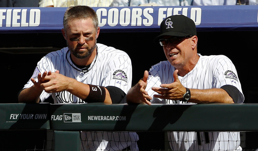 . Colorado Rockies right fielder Michael Cuddyer, left, tallks with bench coach Tom Runnells as the Rockies bat against the New York Mets in the first inning of a baseball game in Denver on Thursday, June 27, 2013. Cuddyer singled in the second inning to push his hitting streak to 24 games, a new personal record as well as a new team record for the Rockies. (AP Photo/David Zalubowski)
