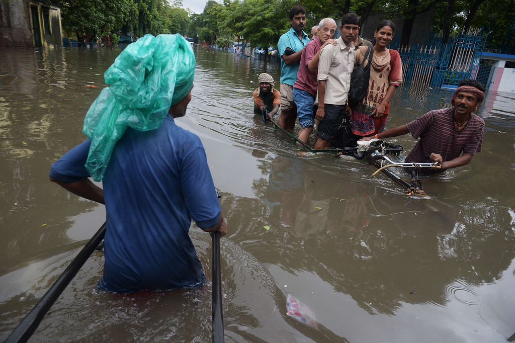 . Indian rickshaw pullers carry passengers through a flooded street in Kolkata on October 26, 2013.  Persistent rain for the last 24 hours has thrown normal life out of gear with reports of water logging at major arterial roads of the city which received 14 cm rainfall, the highest rainfall during the ongoing depression in eastern India. DIBYANGSHU SARKAR/AFP/Getty Images