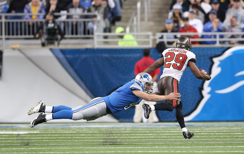 . Quarterback Matthew Stafford #9 of the Detroit Lions attempts to tackle Leonard Johnson #29 of the Tampa Bay Buccaneers after throwing a second quarter interception during the game at Ford Field on November 24, 2013 in Detroit, Michigan.  (Photo by Leon Halip/Getty Images)