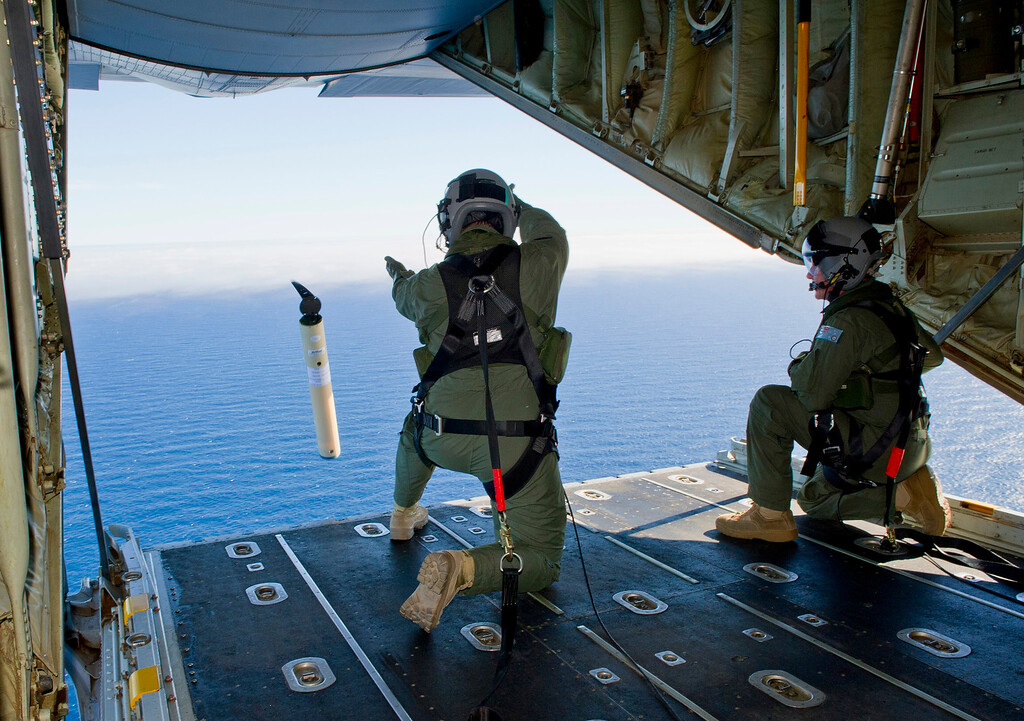 . In this photo provided by the Australia Defence Department March 20, 2014, Royal Australian Air Force Loadmasters Sgt. Adam Roberts, left, and Flight Sgt. John Mancey, launch a Self Locating Data Marker Buoy from a C-130J Hercules aircraft in the southern Indian Ocean as part of the Australian Defense Force\'s assistance to the search for Malaysia Airlines flight MH370. (AP Photo/Australian Defense Department, Justin Brown)