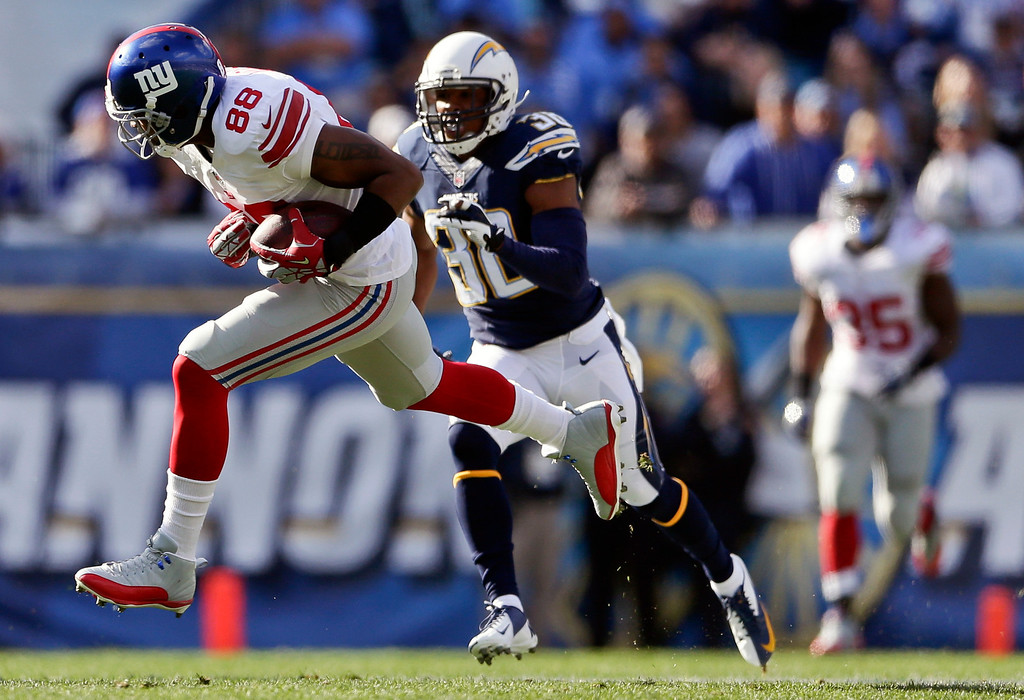 . New York Giants wide receiver Hakeem Nicks (88) pulls in a 51-yard reception as San Diego Chargers strong safety Marcus Gilchrist pursues during the first half of an NFL football game on Sunday, Dec. 8, 2013, in San Diego. (AP Photo/Gregory Bull)