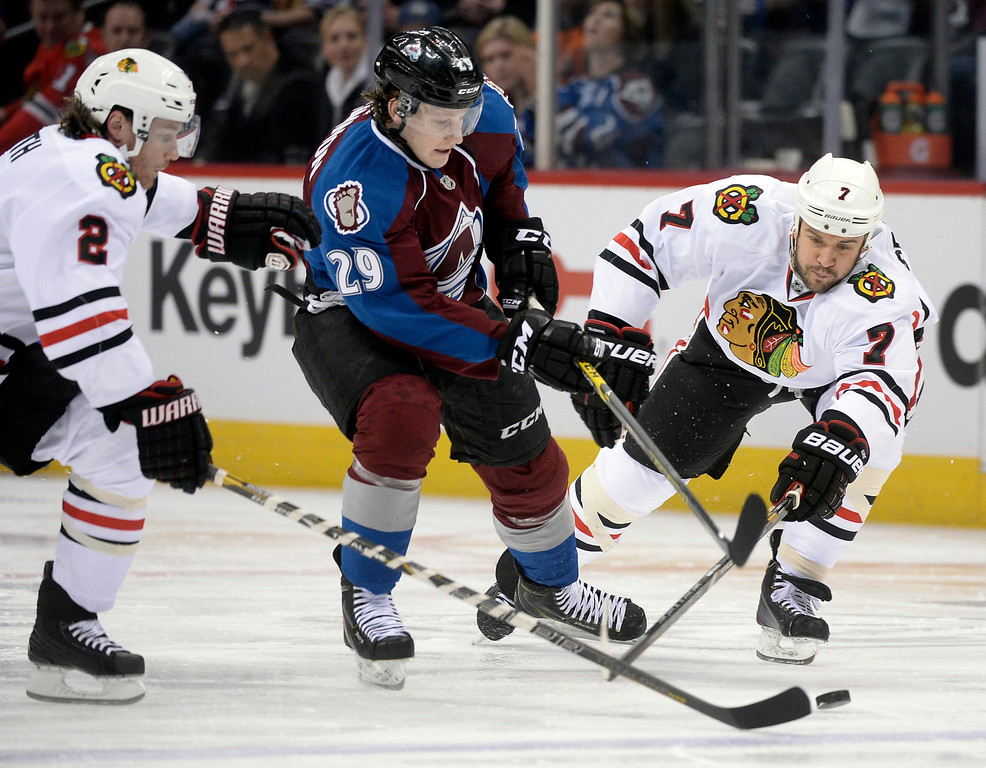 . Colorado center Nathan MacKinnon (29) tried to squeeze the puck between Chicago\'s Duncan Keith (2) and Brent Seabrook (7) in the first period as the Colorado Avalanche hosted the Chicago Blackhawks at the Pepsi Center Wednesday night, March 12, 2014 in Denver, Colorado. (Photo by Karl Gehring/The Denver Post)