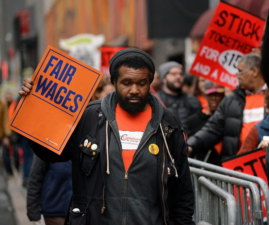 . A protester holds up a placard reading \'fair wages\' as fast food workers and union members demonstrate calling for an increase in the minimum hourly wage to 15 US dollars and the right of workers to join unions, in New York, USA, 05 December 2013.  EPA/PETER FOLEY