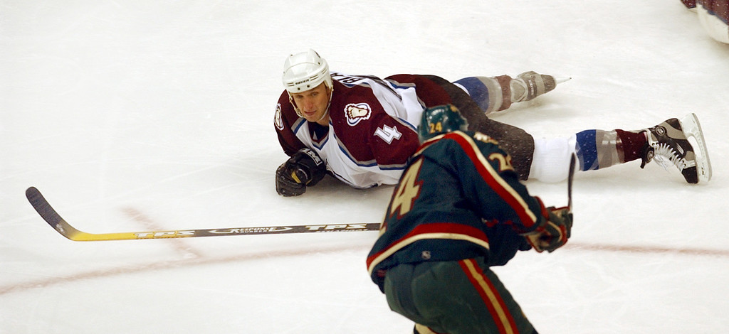 . Avalanche defender Rob Blake goes to the ice to try to block a shot by Minnesota\'s Antti Laaksonen in the second period.  Denver Post photo by Karl Gehring.