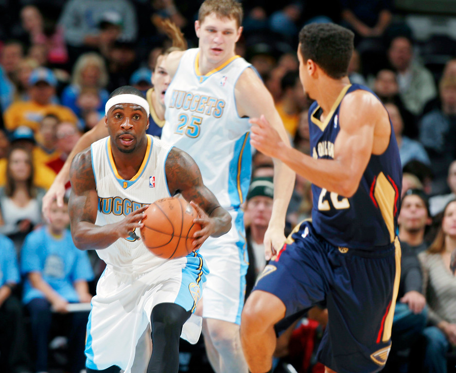 . Denver Nuggets guard Ty Lawson, left, picks up a loose ball as New Orleans Pelicans guard Brian Roberts, front, covers in the first quarter of an NBA basketball game in Denver on Sunday, Dec. 15, 2013. (AP Photo/David Zalubowski)