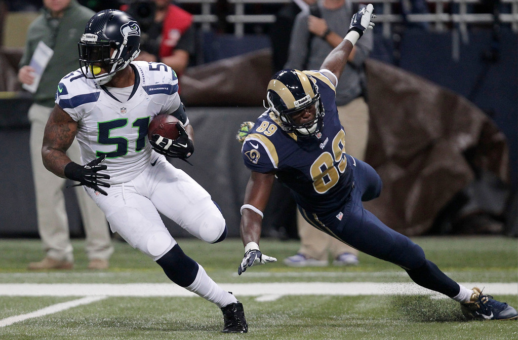 . Seattle Seahawks outside linebacker Bruce Irvin (51) runs against St. Louis Rams tight end Jared Cook (89) after intercepting the pass during the first half of an NFL football game, Monday, Oct. 28, 2013, in St. Louis. (AP Photo/Tom Gannam)