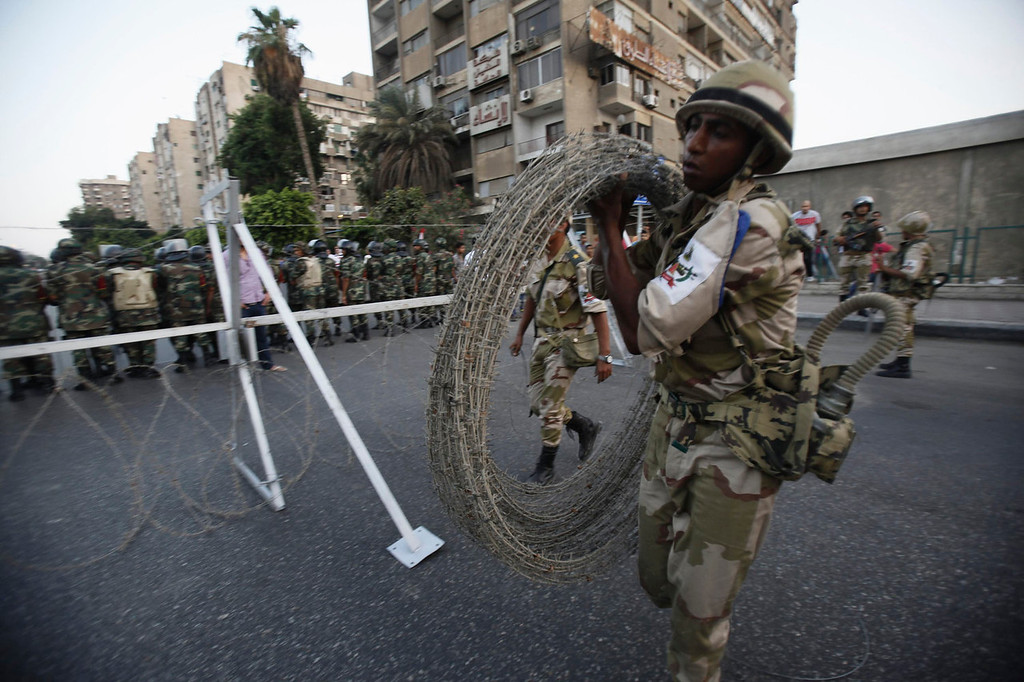 ". A soldier carries barbed wire fencing near army soldiers taking positions in front of protesters who are against Egyptian President Mohamed Mursi, near the Republican Guard headquarters in Cairo July 3, 2013. Egypt\'s armed forces overthrew elected Islamist President Mursi on Wednesday and announced a political transition with the support of a wide range of political, religious and youth leaders. A statement published in Mursi\'s name on his official Facebook page after Sisi\'s speech said the measures announced amounted to ""a full military coup\"" and were \""totally rejected\"". REUTERS/Amr Abdallah Dalsh"