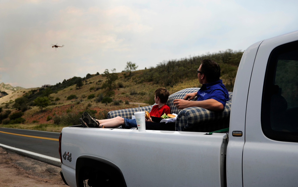 . Ashley Terradez and his son, Zachary, who live near the Waldo Canyon Fire area, stop and eat their lunch as they watch crews fight the fire from the air, Tuesday June 26, 2012. They were on there way to bring the old couch to goodwill. RJ Sangosti, The Denver Post