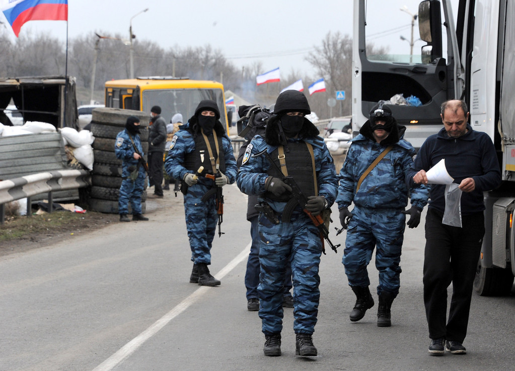 . Armed masked men who call  themselves members of Ukraine\'s disbanded elite Berkut riot police force check driver\'s documents at their checkpoint under a Russian flag on a highway that connect Black Sea Crimea  peninsula to mainland Ukraine near the city of Armyansk, on February 28, 2014.AFP PHOTO / VIKTOR DRACHEV/AFP/Getty Images