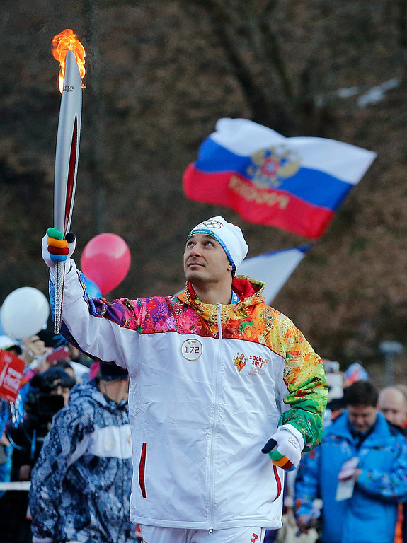 . Former Olympic bob sleigher Alexey Voyevoda of Russia carries the Olympic torch in the mountain village of Krasnaya Polyana, Russia, ahead of the Sochi 2014 Winter Olympics, Wednesday, Feb. 5, 2014. (AP Photo/Christophe Ena)