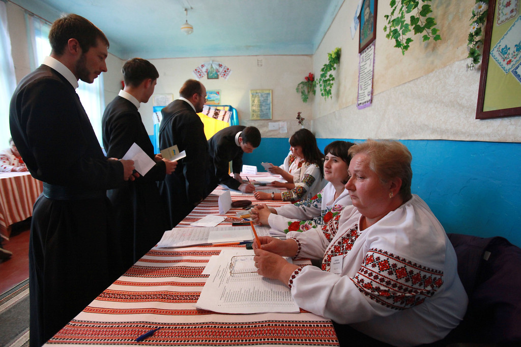 . Orthodox monks receive their ballots during voting in a presidential election at polling station in the village of Fiyna in the Lviv region of western Ukraine, Sunday, May 25, 2014. (AP Photo/Petro Zadorozhnyy)