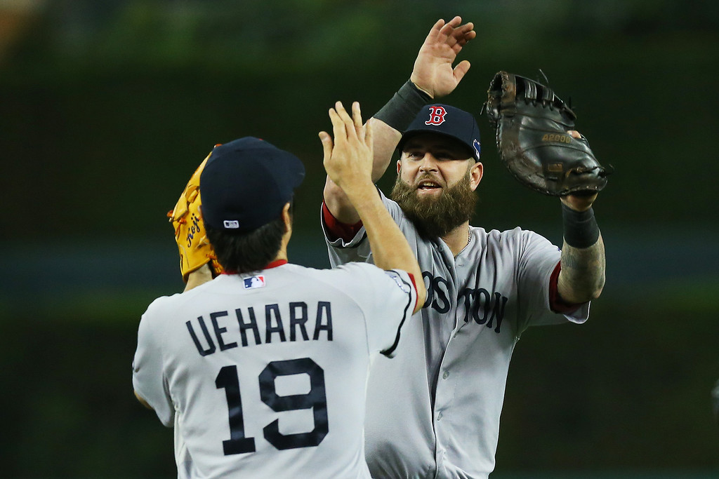 . Mike Napoli #12 and Koji Uehara #19 of the Boston Red Sox celebrate their 1 to 0 win over the Detroit Tigers during Game Three of the American League Championship Series at Comerica Park on October 15, 2013 in Detroit, Michigan.  (Photo by Ronald Martinez/Getty Images)