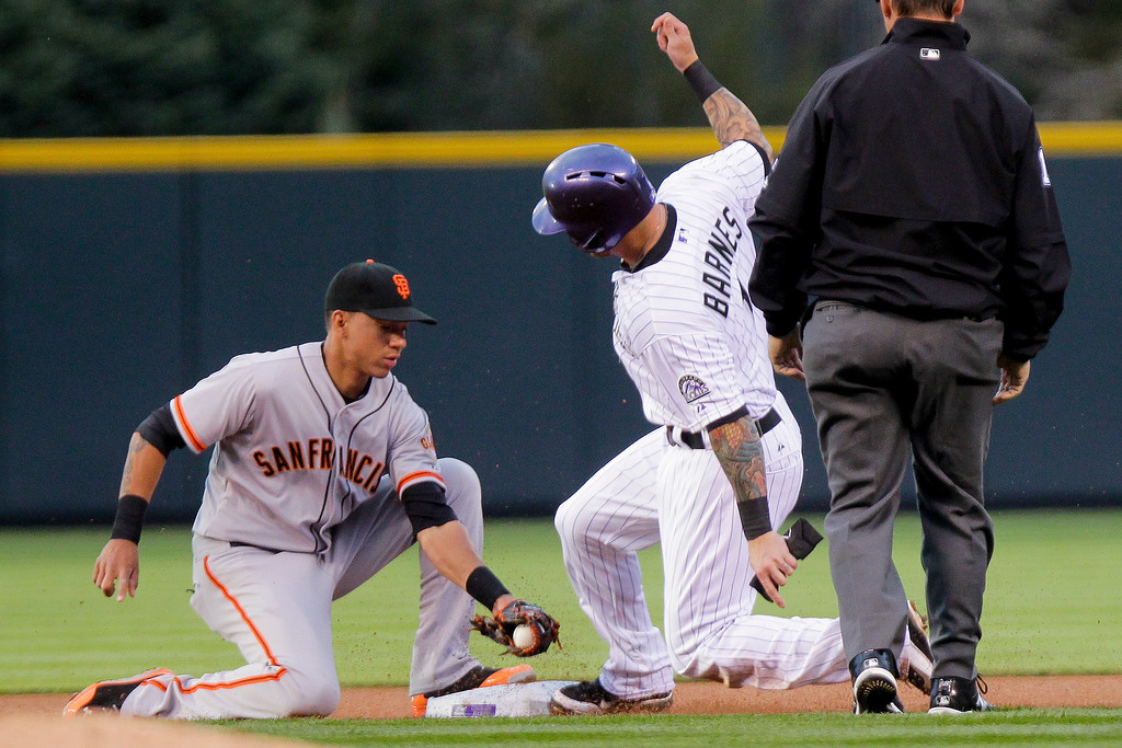 . Colorado Rockies\' Brandon Barnes, center, steals second base with San Francisco Giants\' Ehire Adrianza covering during the first inning of a baseball game, Tuesday, April 22, 2014, in Denver. (AP Photo/Barry Gutierrez)