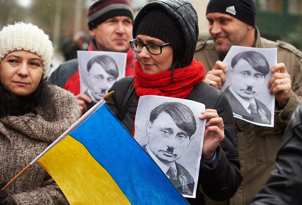 . Protesters hold portraits of Russian President Vladimir Putin during a demonstration organized by a trade union \'Solidarity\' against the Russian military actions in Crimea, in front of the Russian Consulate General headquarters in Gdansk, Poland, 15 March 2014.  EPA/ADAM WARZAWA