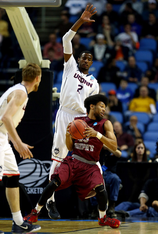 . BUFFALO, NY - MARCH 20: DeAndre Bembry #43 of the Saint Joseph\'s Hawks goes to the basket as DeAndre Daniels #2 of the Connecticut Huskies defends during the second round of the 2014 NCAA Men\'s Basketball Tournament at the First Niagara Center on March 20, 2014 in Buffalo, New York.  (Photo by Elsa/Getty Images)