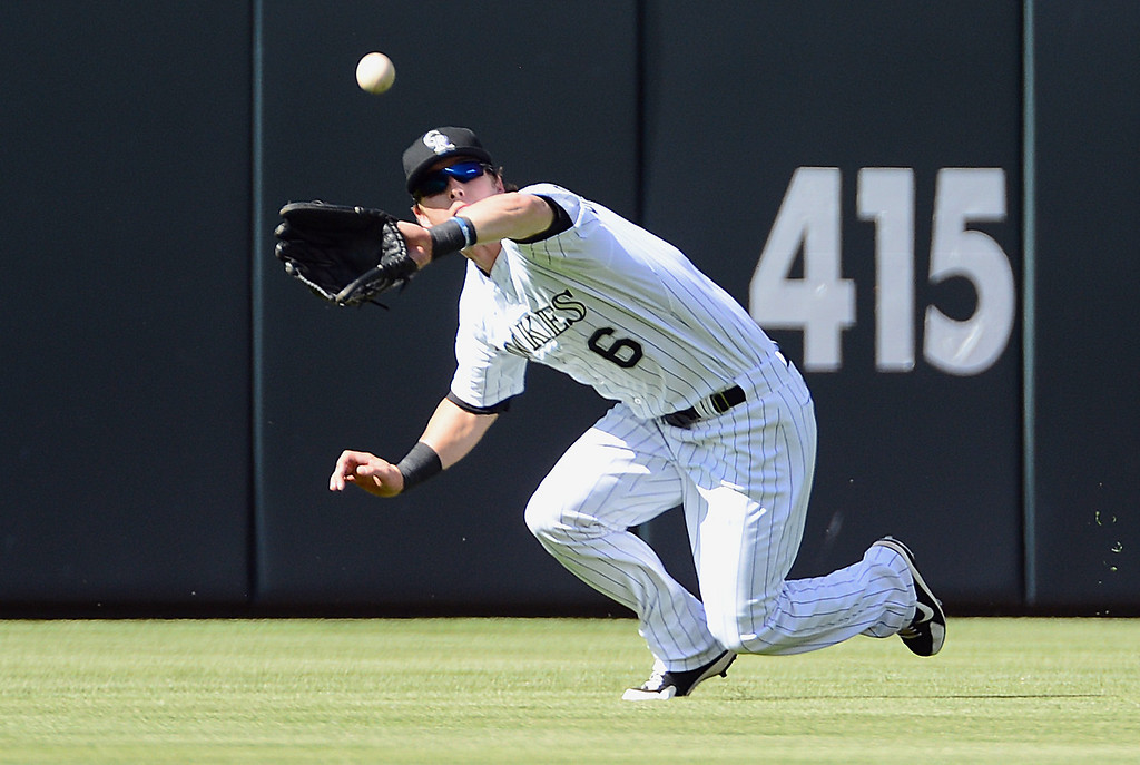 . Corey Dickerson #6 of the Colorado Rockies catches a fly ball against the New York Mets in the second inning of the game at Coors Field on June 27, 2013 in Denver, Colorado. Photo by Garrett W. Ellwood/Getty Images)