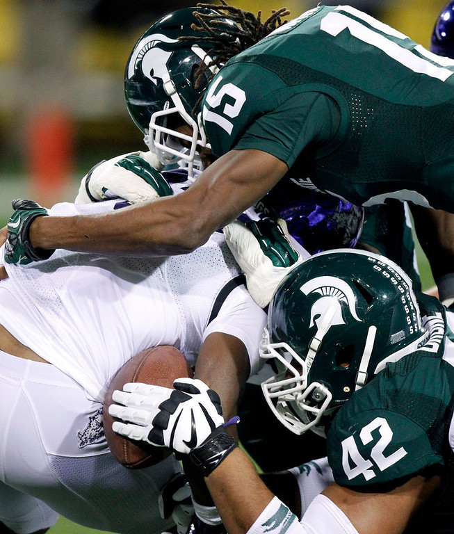 . Michigan State defensive end Denzel Drone, bottom, pulls the ball away from TCU running back B.J. Catalon, center, as Michigan State cornerback Trae Waynes, top,hits Catalon during the first half of the Buffalo Wild Wings Bowl NCAA college football game, Saturday, Dec. 29, 2012, in Tempe, Ariz. Catalon\'s forward progress was stopped causing the referees to blow the play dead. (AP Photo/Paul Connors)