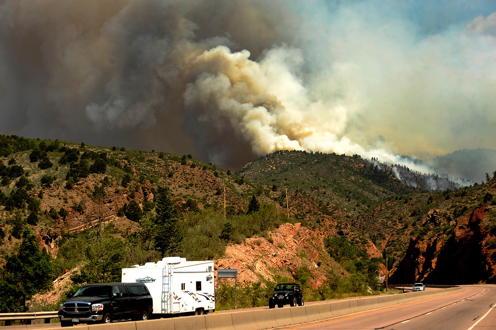 . Evacuees head east on Highway 24 towards Manitou Springs as they race to get away from the fire. The Waldo Canyon fire continues to burn northwest of Manitou Springs, Colorado on June 24th, 2012.  The fire, which is threatening the Cedar Heights neighborhood, has already consumed over 2,500 acres with 0% containment. Helen H. Richardson, The Denver Post
