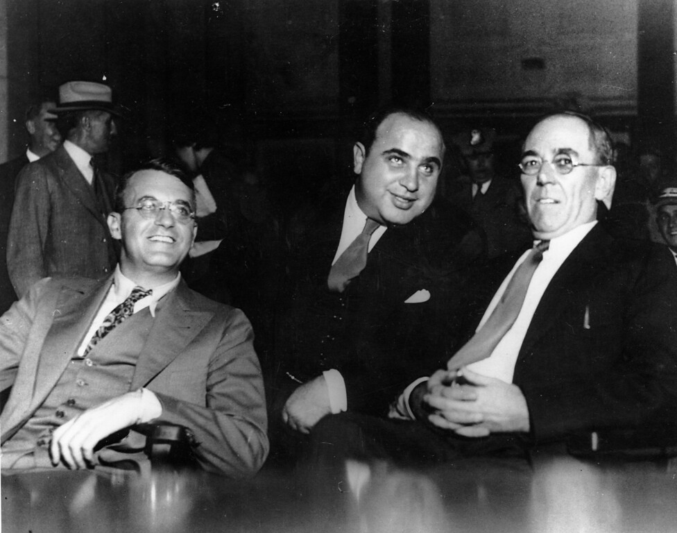 . Al Capone faces a jury in Federal Court in Chicago for income tax evasion on Oct. 7, 1931.  To Capone\'s left is Michael Ahern, his chief legal defense attorney. To the right is attorney Albert Fink.  (AP Photo)