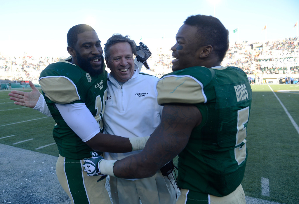 . Colorado State Rams football players, Trent Matthews, left, and Kapri Bibbs, right, congratulate head coach, Jim McElwain, after dousing him with Powerade on the sidelines Saturday afternoon, November 30, 2013. The Rams defeated Air Force 58-13. (Photo By Andy Cross/The Denver Post)