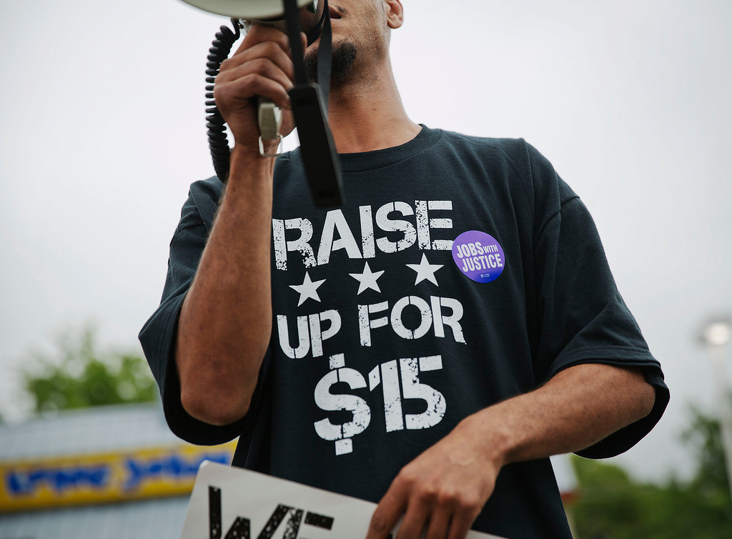 . Long John Silver\'s employee Antwon Brown, 31, uses a bullhorn while wearing  a shirt advocating for higher wages during a protest outside a Long John Silver\'s restaurant, Thursday, May 15, 2014, in Atlanta.  (AP Photo/David Goldman)