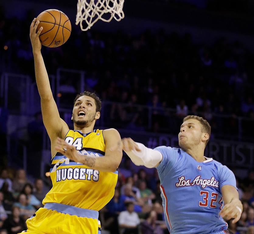 . The Los Angeles Clippers\' Blake Griffin covers a shot from the Denver Nuggets\' Evan Fournier during the second half of a preseason NBA basketball game on Saturday, Oct. 19, 2013, in Las Vegas. The Clippers defeated the Nuggets in overtime 118-111. (AP Photo/Isaac Brekken)