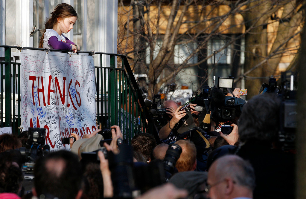 . Annie Blagojevich, daughter of former Illinois Gov. Rod Blagojevich, watches as her father is surrounded by the media in front of their home Wednesday, March 14, 2012 in Chicago. The 55-year-old Democrat is due to report to a prison in Colorado on Thursday to begin serving a 14-year sentence, making him the second Illinois governor in a row to go to prison for corruption. (AP Photo/M. Spencer Green)