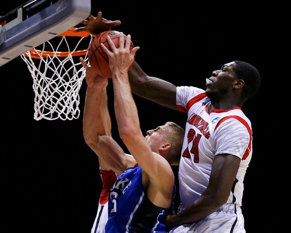 . Duke Blue Devils forward Mason Plumlee (5) is stopped from scoring in the first half by Louisville Cardinals forward Montrezl Harrell (24) during their Midwest Regional NCAA men\'s basketball game in Indianapolis, Indiana, March 31, 2013. REUTERS/Matt Sullivan