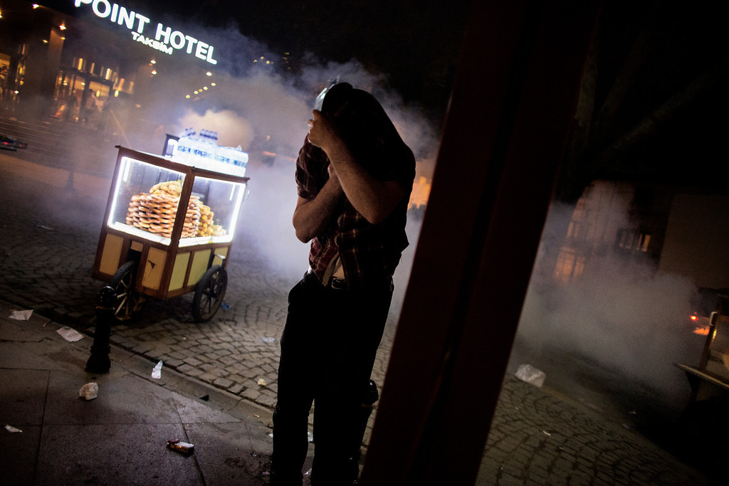 . A street food vendor cover his face to protect himself from tear gas lobbed by Turkish riot police officers to disperse demonstrators in Gezi Park in Istanbul June 15, 2013.Turkish police stormed an Istanbul park on Saturday after protesters defied an ultimatum from Prime Minister Recep Tayyip Erdogan to end their occupation of the site, in a major escalation of more than two weeks of anti-government unrest.   MARCO LONGARI/AFP/Getty Images