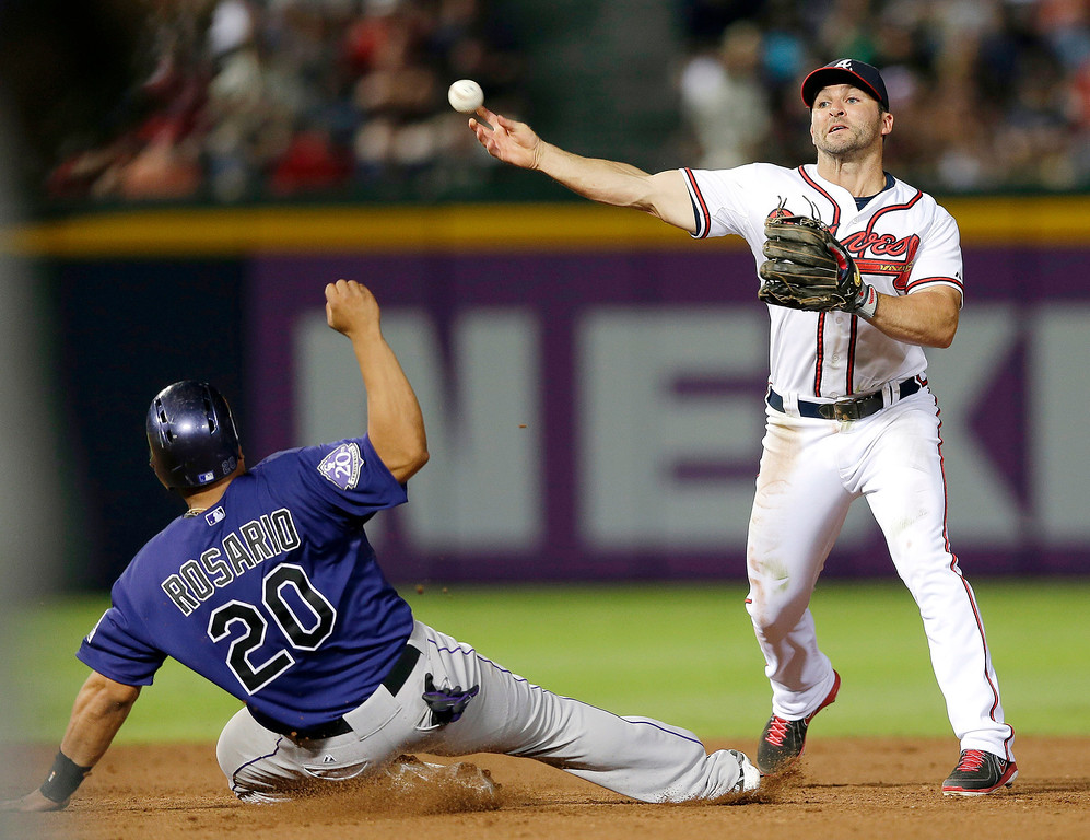 . Atlanta Braves second baseman Dan Uggla forces out Colorado Rockies\' Wilin Rosario (20) at second base as he turns a double play on a Nolan Arenado ground ball in the eight inning of a baseball game in Atlanta, Monday, July 29, 2013. (AP Photo/John Bazemore)