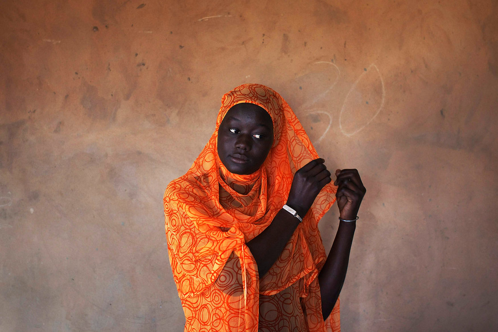 . Coumba Faye, 19, fixes her headscarf in her house in the village of Ndande, May 19, 2013. Every year, inhabitants of the village take part in a Sufi Muslim ceremony called Gamou-Ndande. The ceremony combines nights of praying and chanting as well as traditionally animist ceremonies. Picture taken May 19, 2013.  REUTERS/Joe Penney