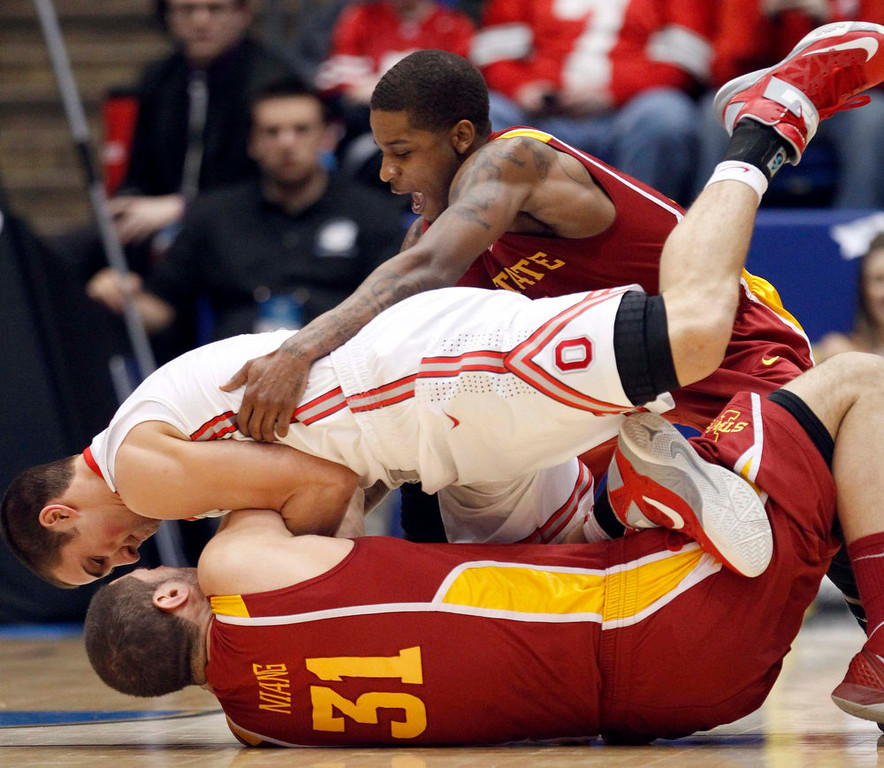 . Iowa State Cyclones forward Georges Niang (bottom) and Ohio State Buckeyes guard Aaron Craft (C) wrestle for the loose ball as Cyclones guard Korie Lucious (top) pulls off Craff during the first half of their third round NCAA tournament basketball game in Dayton, Ohio March 24, 2013.   REUTERS/Matt Sullivan