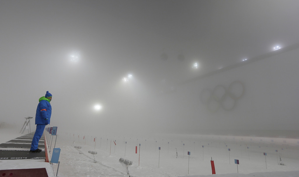 . A race officer stands in the shooting range after the men\'s biathlon 15k mass start was postponed for one day because of fog, at the 2014 Winter Olympics, Sunday, Feb. 16, 2014, in Krasnaya Polyana, Russia. (AP Photo/Kirsty Wigglesworth)