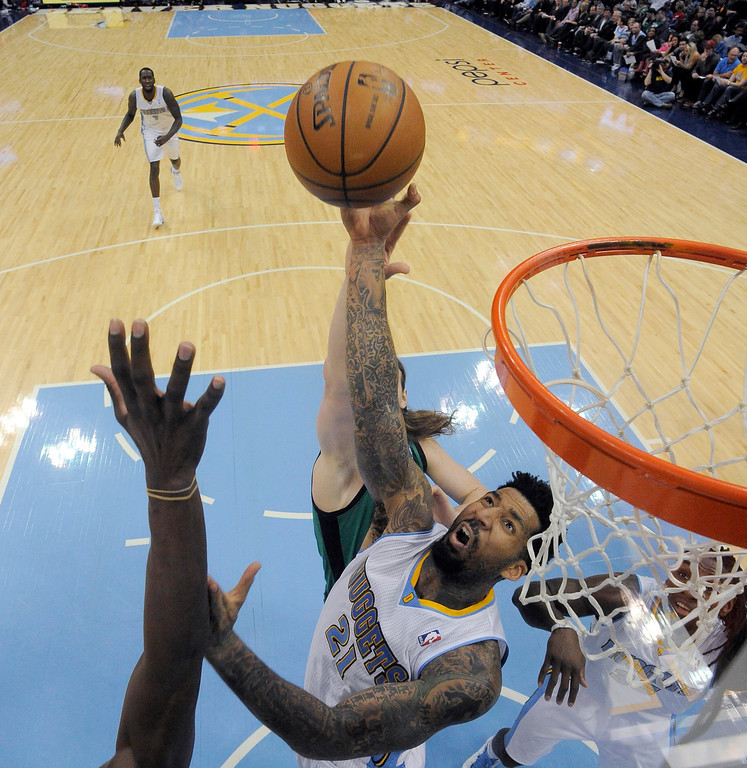 . Denver Nuggets small forward Wilson Chandler (21) hauls down an offensive rebound from Boston Celtics center Kelly Olynyk (41) during the second quarter January 7, 2014 at Pepsi Center. (Photo by John Leyba/The Denver Post)