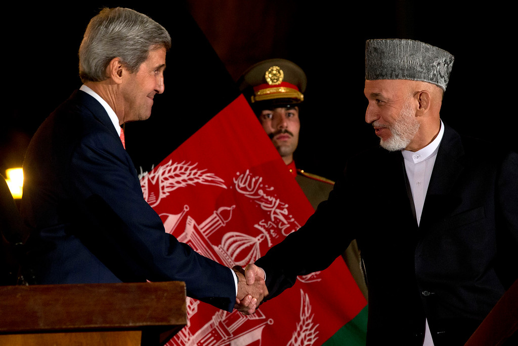 . U.S. Secretary of State John Kerry shakes hands with Afghan President Hamid Karzai after they made remarks during a news conference at the Presidential Palace during an unannounced stop in Kabul, Afghanistan, on Saturday, Oct. 12, 2013, as a deadline approaches for a security deal about the future of U.S. troops in the country. (AP Photo/Jacquelyn Martin, Pool)
