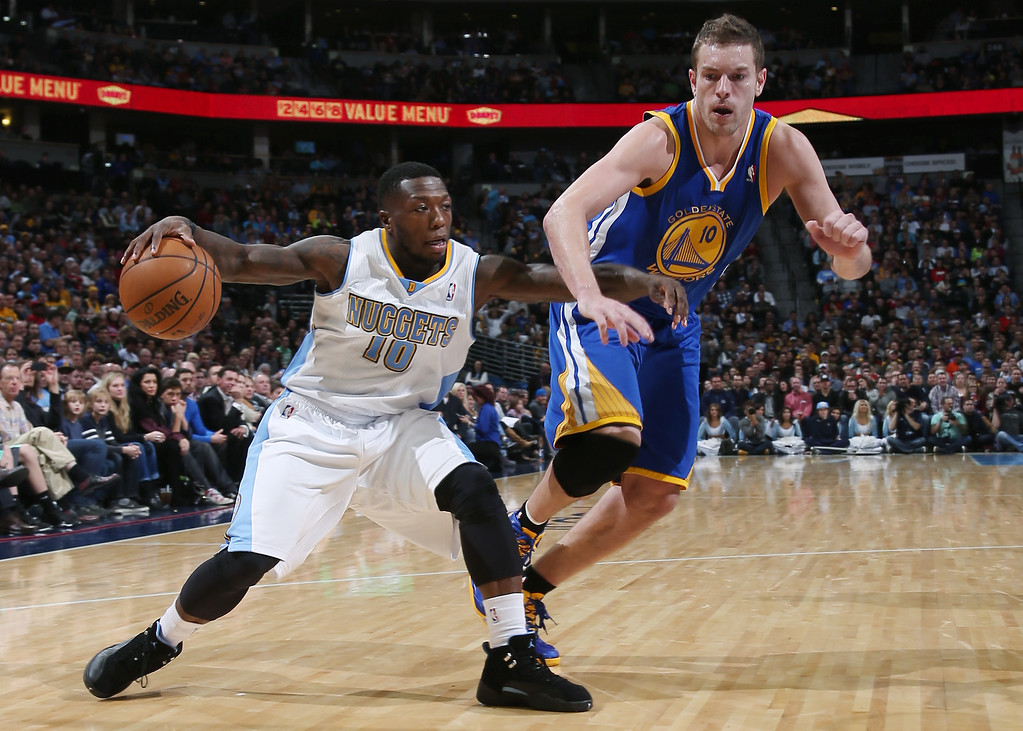 . Denver Nuggets guard Nate Robinson, left, works ball inside as Golden State Warriors forward David Lee defends during the fourth quarter of the Warriors\' 89-81 victory in an NBA basketball game in Denver on Monday, Dec. 23, 2013. (AP Photo/David Zalubowski)