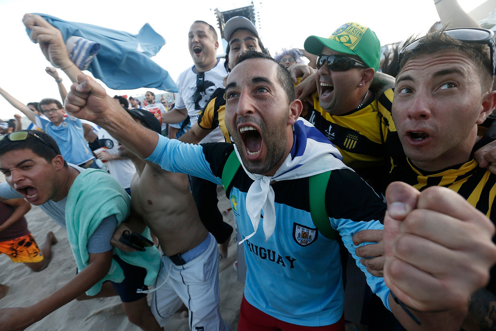 . Uruguay soccer fans celebrate a goal against Costa Rica inside the FIFA Fan Fest area on Copacabana beach in Rio de Janeiro, Brazil, Saturday, June 14, 2014. (AP Photo/Silvia Izquierdo)