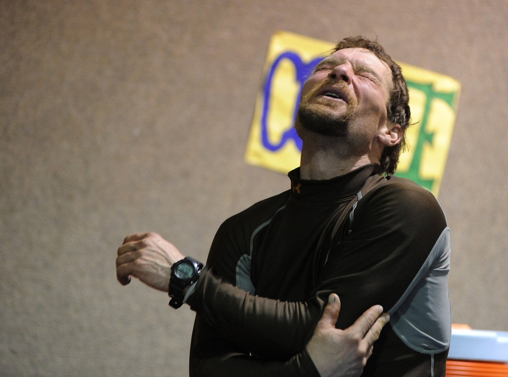 . Musher Jason Mackey winces with pain as he moves his arm in the school cafeteria at the Nikolai, Alaska, checkpoint during the Iditarod Trail Sled Dog Race on Tuesday, March 4, 2014. (AP Photo/Anchorage Daily News, Bob Hallinen)