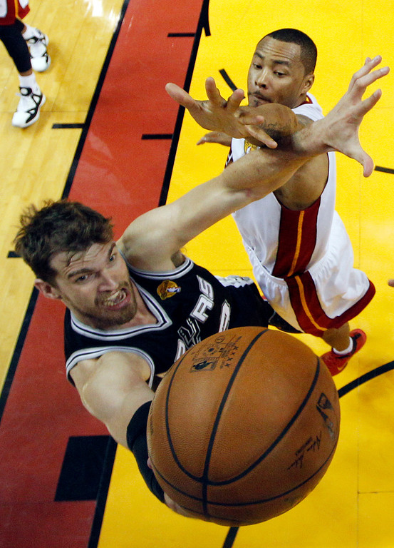 . San Antonio Spurs center Tiago Splitter (22) drives to the basket over Miami Heat forward Rashard Lewis (9) and Miami Heat center Chris Bosh (1)during the first half in Game 3 of the NBA basketball finals, Tuesday, June 10, 2014, in Miami. (AP Photo/Lynne Sladky)