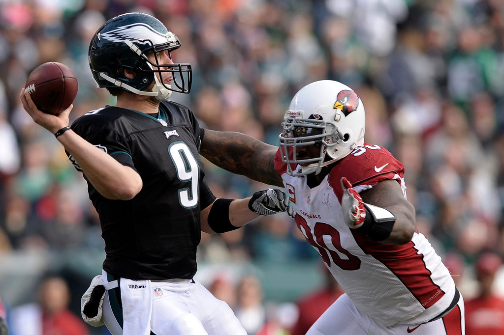 . Philadelphia Eagles\' Nick Foles, left, passes under pressure from Arizona Cardinals\' Darnell Dockett during the first half of an NFL football game, Sunday, Dec. 1, 2013, in Philadelphia. (AP Photo/Michael Perez)