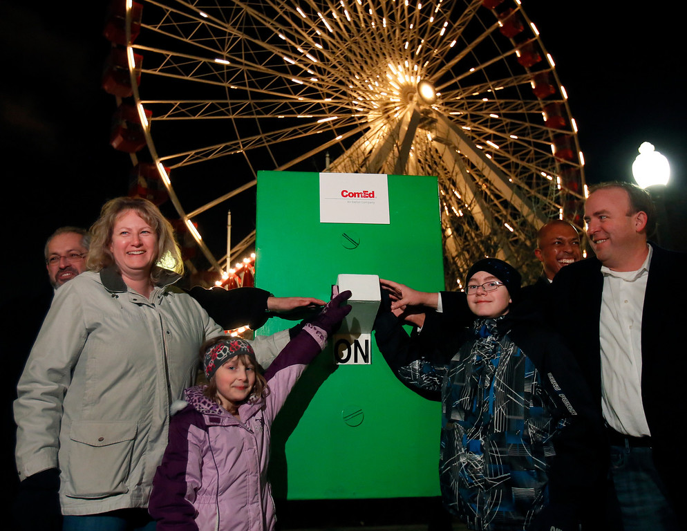 . Senior Vice President of ComEd Fidel Marquez, ComEd customer Kathy Reiser, her children Caitlin and Ramsey, Navy Pier director of External Communications Nick Shields and Ald. Brendan Reilly, 42 Ward, pose for a photo as they turn off the lights of the Ferris Wheel at Navy Pier in observation of Earth Hour in Chicago on Saturday, March 23, 2013. (AP Photo/ComEd, Charles Osgood)